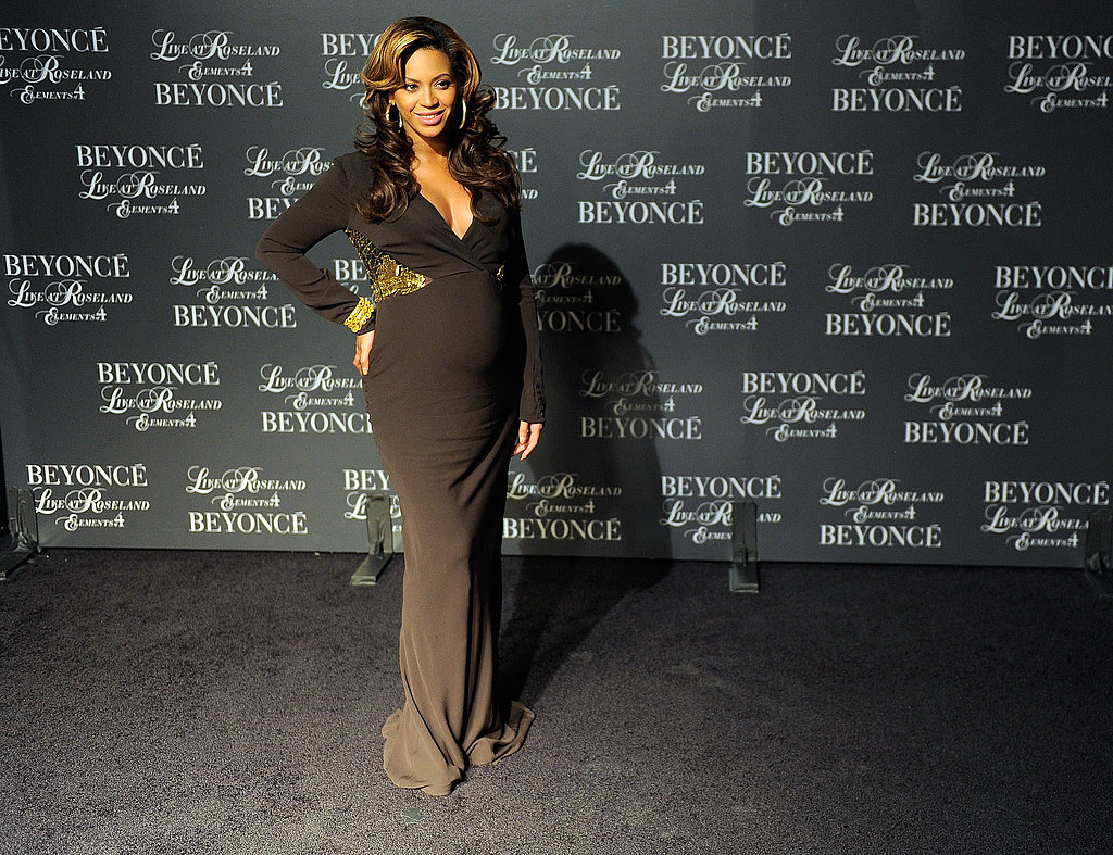 Beyoncé Knowles shows off her pregnant belly in a black dress.