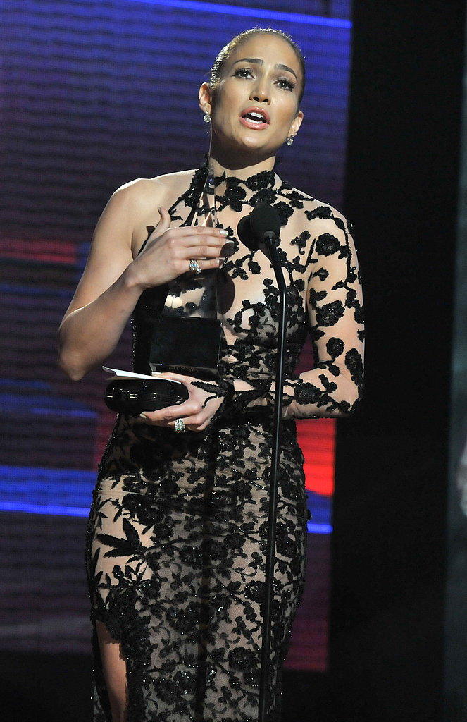 Jennifer Lopez accepted an American Music Award in a black lace dress.