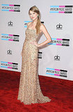 Taylor Swift wore a long gold dress to the American Music Awards.