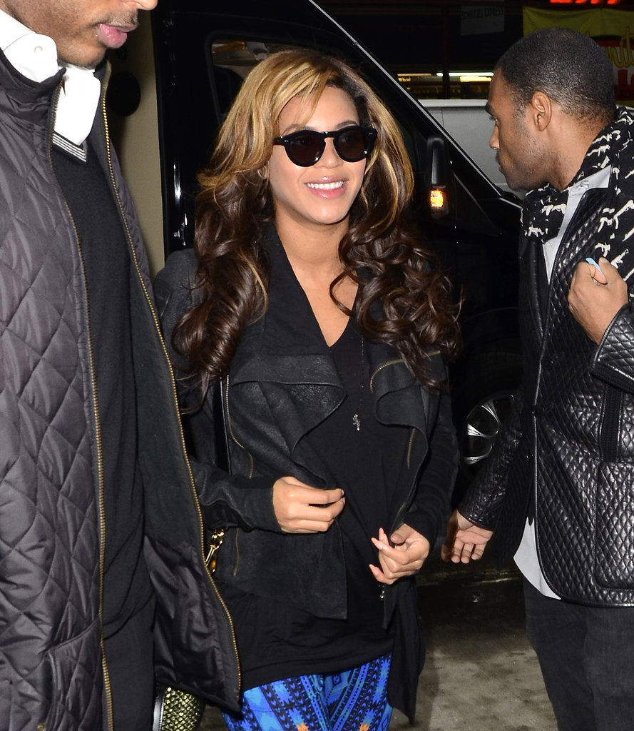 Beyoncé Knowles wearing blue pants and a leather jacket.