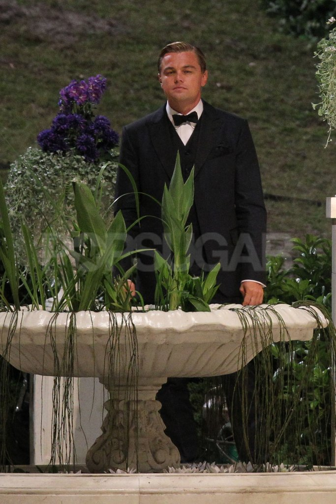 Leonardo DiCaprio walked around a garden on set.