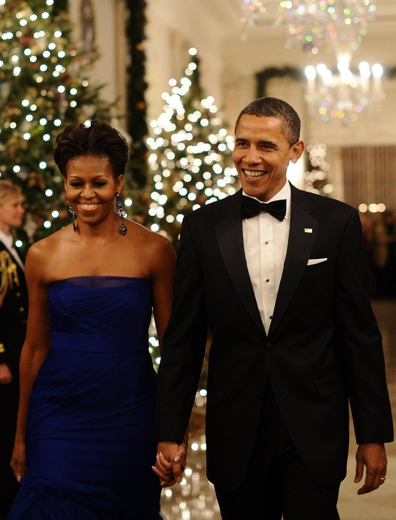 Barack and Michelle Obama arrive in the East Room of the White House to attend a reception for Kennedy Center Honorees in December.