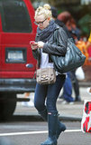 Dakota Fanning checks her iPhone, which is wrapped in a bright pink case.