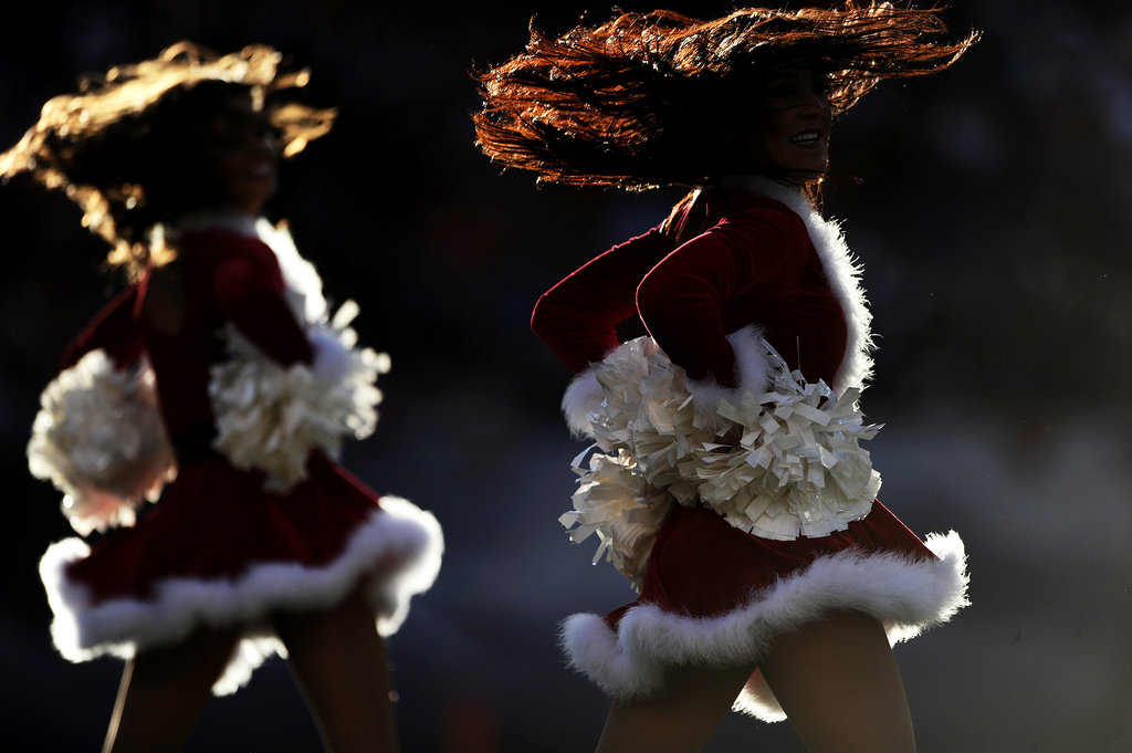 Denver Broncos cheerleaders dance in their holiday uniforms.