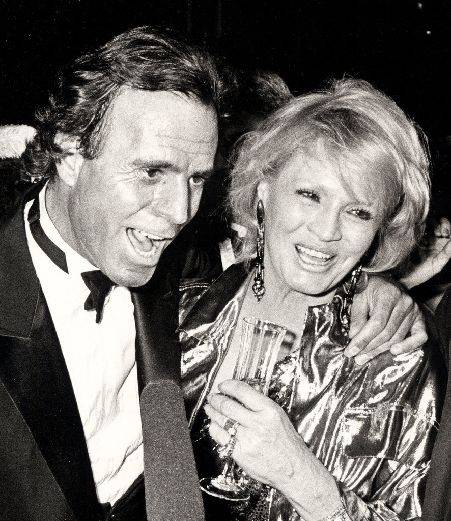 Julio Iglesias, father to Enrique Iglesias, parties it up with Angie Dickinson at a New Year's Eve party in 1985.