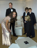 Kate talks to a little boy at the Absolute Return for Kids (ARK) Gala Dinner, which supports the Foundation of Prince William and Prince Harry.