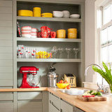 Store your punchy, brightly hued appliances alongside other colorful dishes to liven up a traditional kitchen. Choose all warm shades — or all cool — for shelves that look neatly coordinated. Source