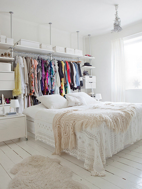 For colorful, unexpected clothing storage, skip the headboard and turn that space into a closet instead. Color-coordinate the items and keep the rest of the decor clean and simple for a fresh, dress-up-ready bedroom. Source