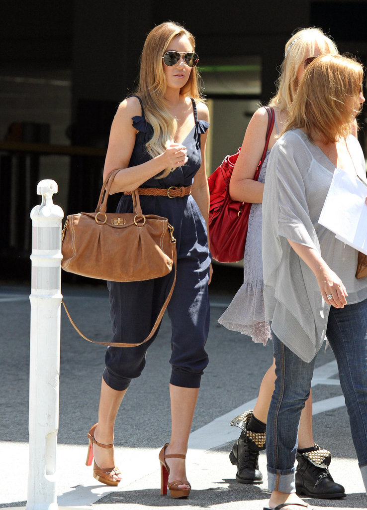 In the Summer of 2010, Lauren continued her love affair with tan accessories, and this time paired them with an adorable navy jumpsuit and Ray-Ban aviators. Since it's probably too chilly to wear a romper right now, save this look for a day outing when the weather warms up.         Platforms by Christian LouboutinSatchels by Fiorelli