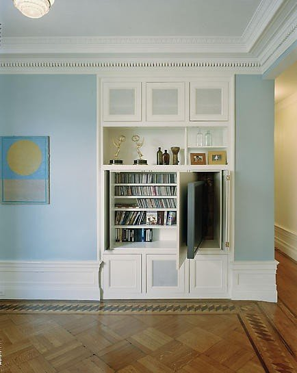 A compartment in this built-in shelving unit allows the TV to be tucked out of sight when not in use. Meanwhile, screened cabinet doors hide cable boxes, DVRs, and such without getting in the way of the remote signal. Source