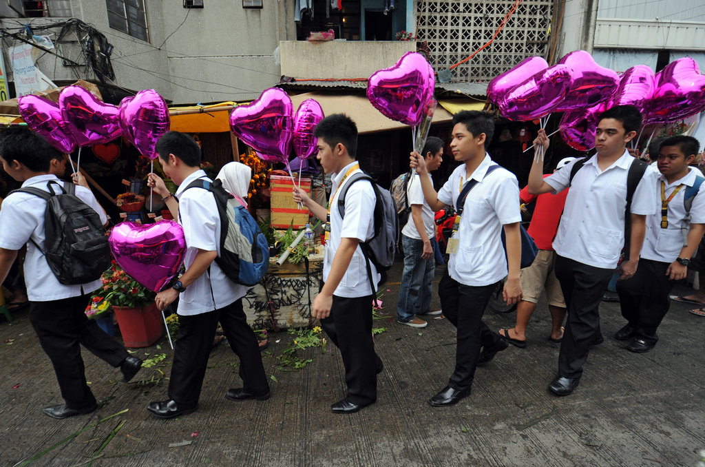 Students holding heart-shaped balloons walk past flower stalls on their way to school on Valentine's Day in Manila.