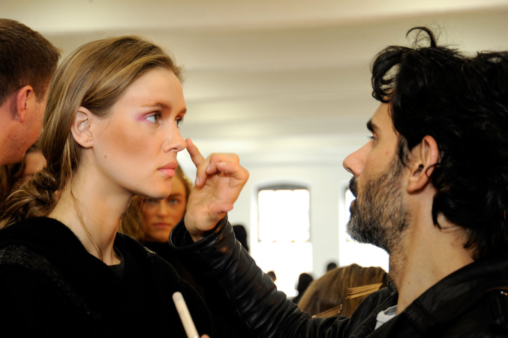 Key artist James Kaliardos checks the progress of a model's makeup.