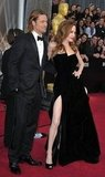Angelina Jolie showed off her sexy high slit gown posing next to Brad Pitt.