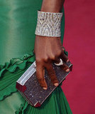 Viola's arm candy in the form of a statement cuff and glittering Judith Leiber clutch finished her look.