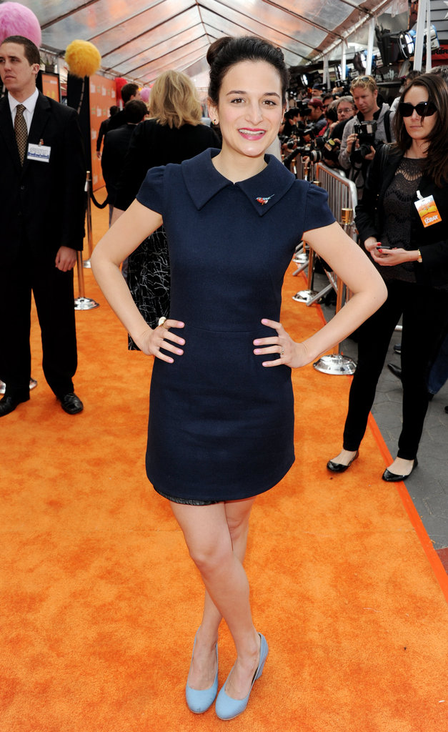 Jenny Slate posing on the orange carpet.