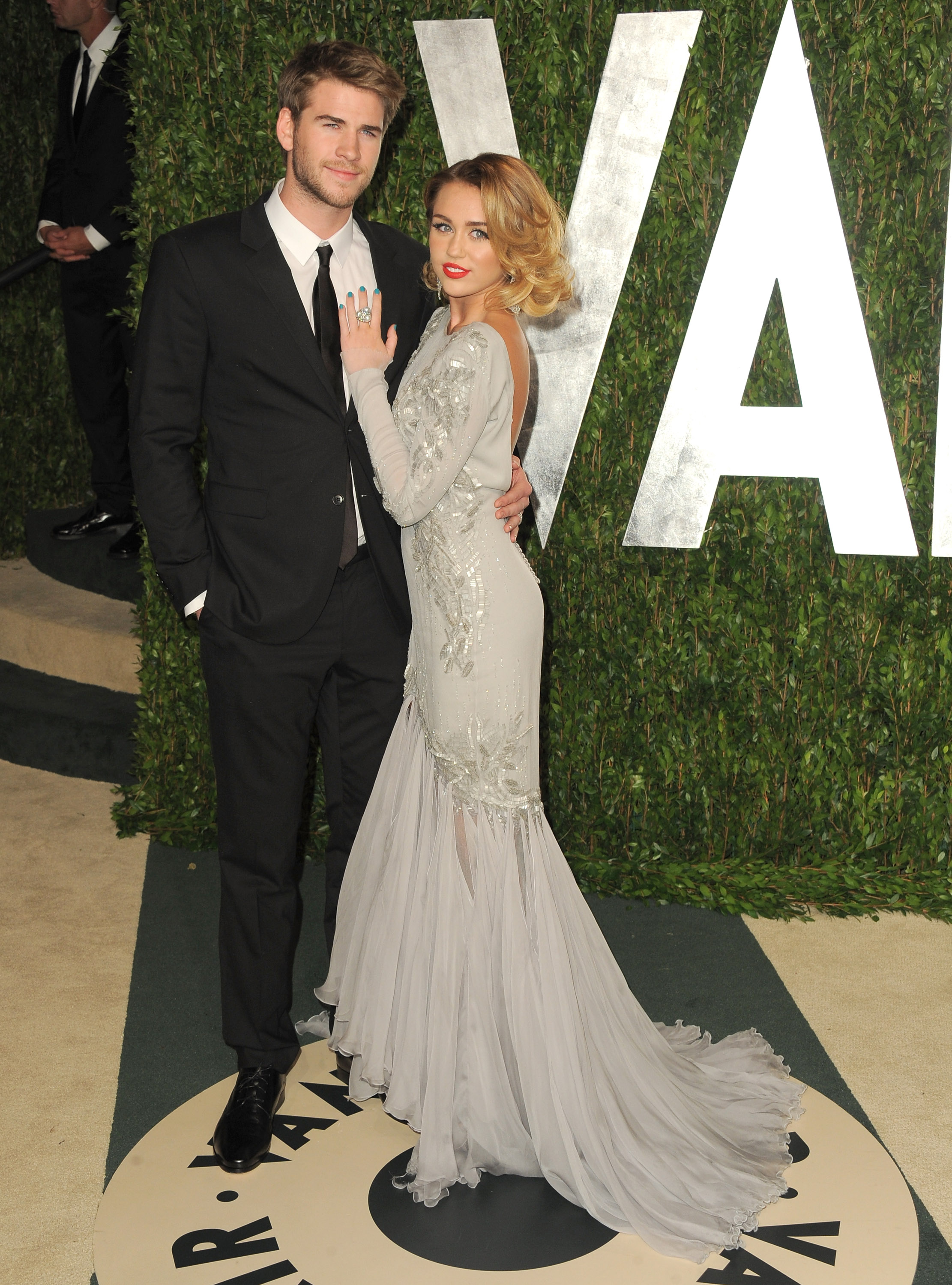 Miley holds on to her man Liam at the Vanity Fair party.