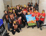 Danny Devito and Zac Efron posed with a poster from their film and a group of kids.