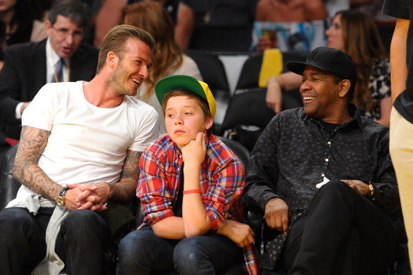 David and Brooklyn Beckham sitting front row with Denzel Washington.