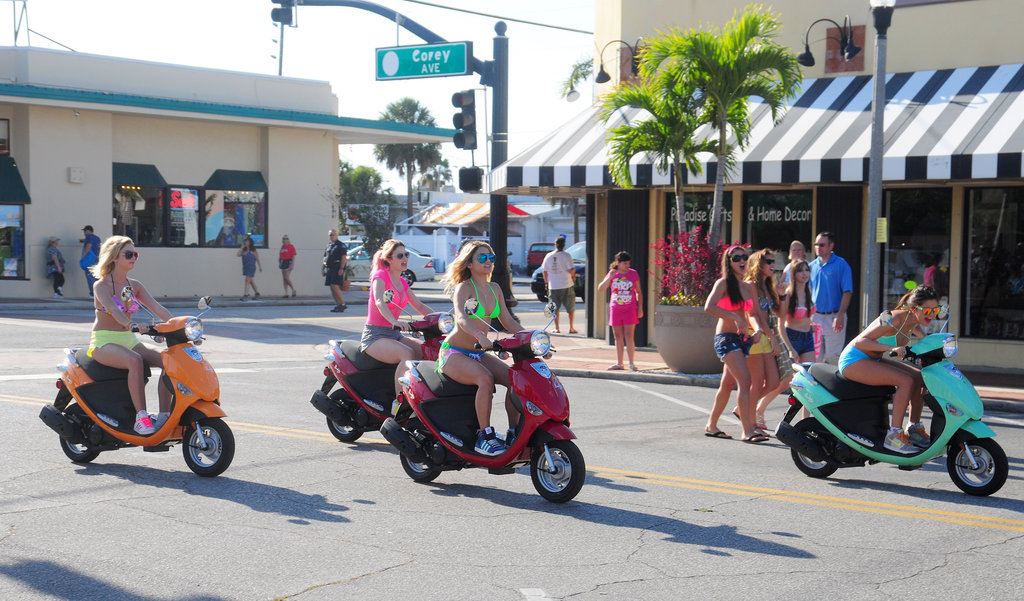 The bikini-clad girls rode their scooters.