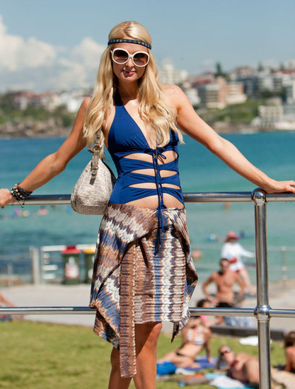 Paris Hilton wore white circle sunglasses and a blue bathing suit with cutouts to Bondi Beach in Australia.