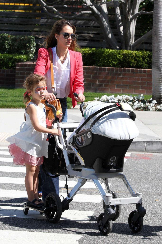 Jessica Alba wore a bright coral blazer as Honor Warren got a ride on baby Haven's stroller.