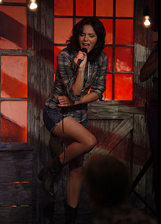 Karen wears a plaid shirt with denim cutoffs and boots.