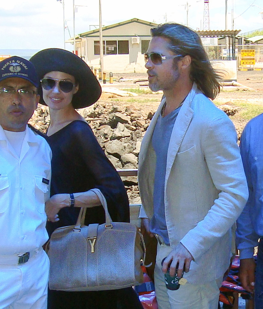Angelina Jolie wore a black large-brimmed hat and carried her YSL bag accompanied by Brad Pitt while traveling back from the Galapagos Islands.