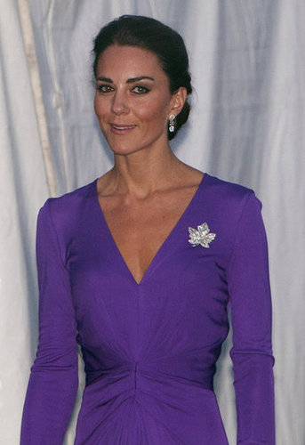 A close-up of the front-cinched detail on her purple Issa dress, as well as her sparkly maple-leaf brooch.