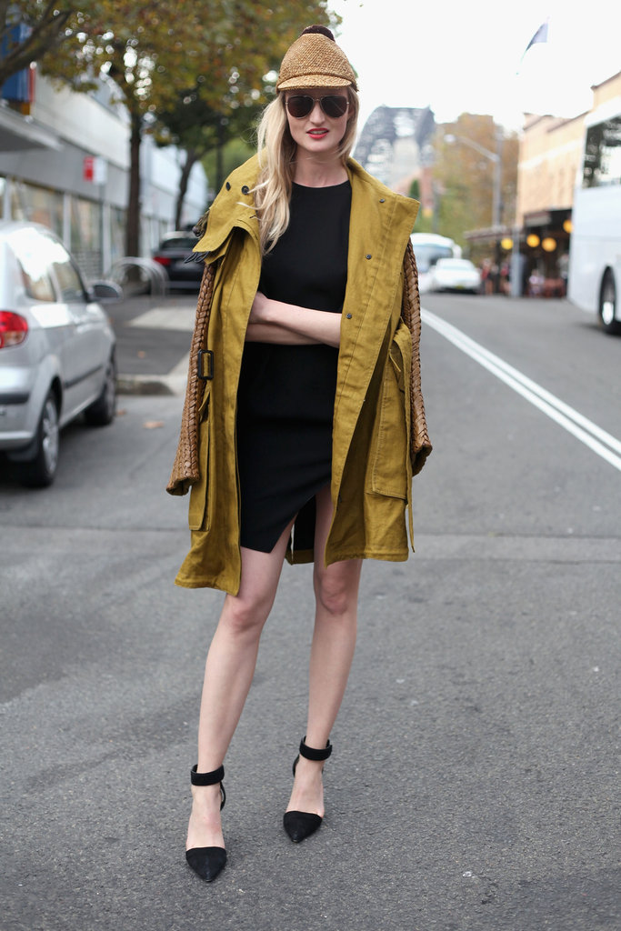 Street-style photographer Candice Lake rocked a cool woven jute hat with a minimalist LBD, ecru-colored topper, and pointy ankle-strap heels.