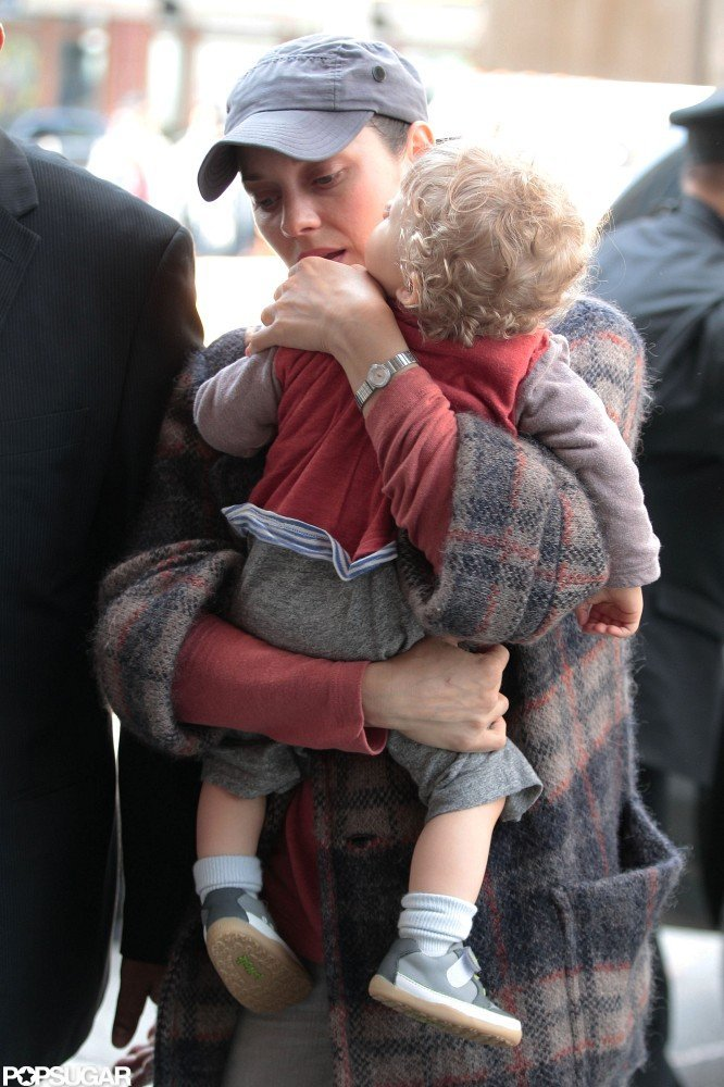 Marion Cotillard carried her son Marcel into her NYC hotel.