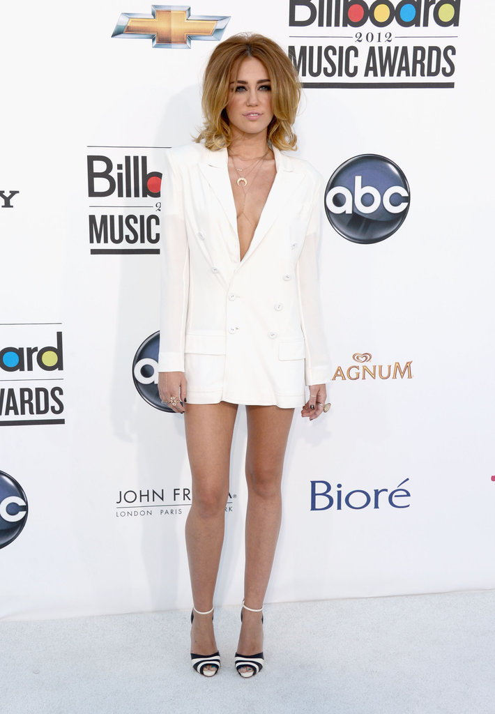 Miley Cyrus opted for a sexier version of menswear-inspired styles in a daring white, V-front Jean Paul Gaultier blazer-cum-dress at the Billboard Music Awards. She finished the look with supercute ankle-strap Christian Louboutin heels.