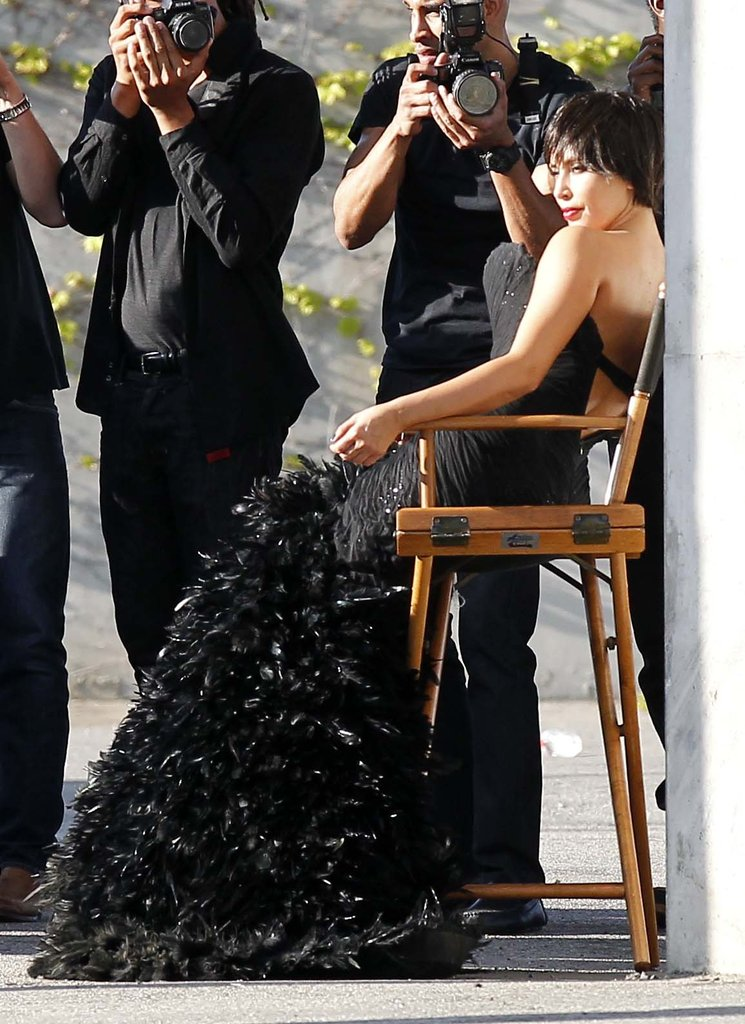 Kim Kardashian posed in a director's chair wearing a glamorous black gown.