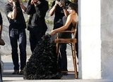 Kim Kardashian posed up in a director's chair as photographers took her picture.