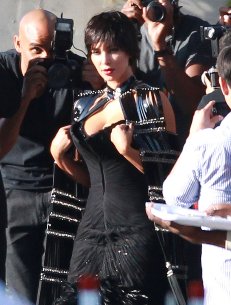 Kim Kardashian adjusted her dress while shooting for Vogue Italia.