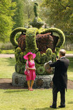 A woman posed by a Diamond Jubilee floral crown installation in St. James's Park.