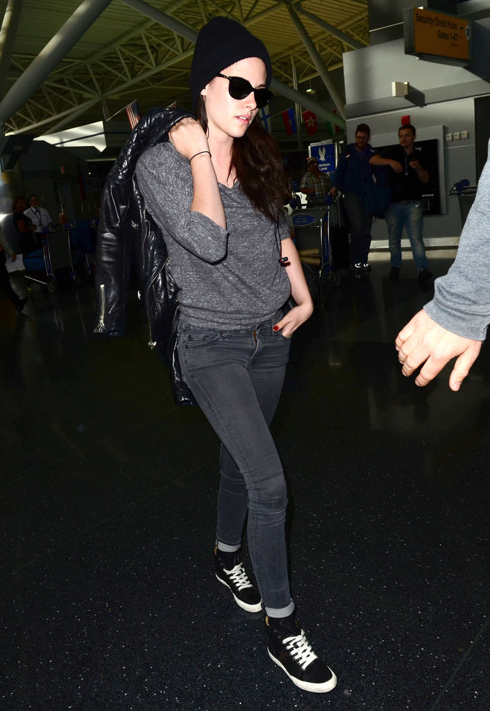 Kristen Stewart landed at JFK wearing sneakers and a gray sweatshirt.