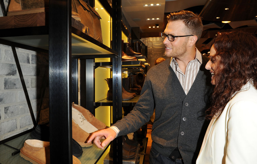 Tom Brady took a look at the different shoes at the opening of Ugg For Men in NYC.