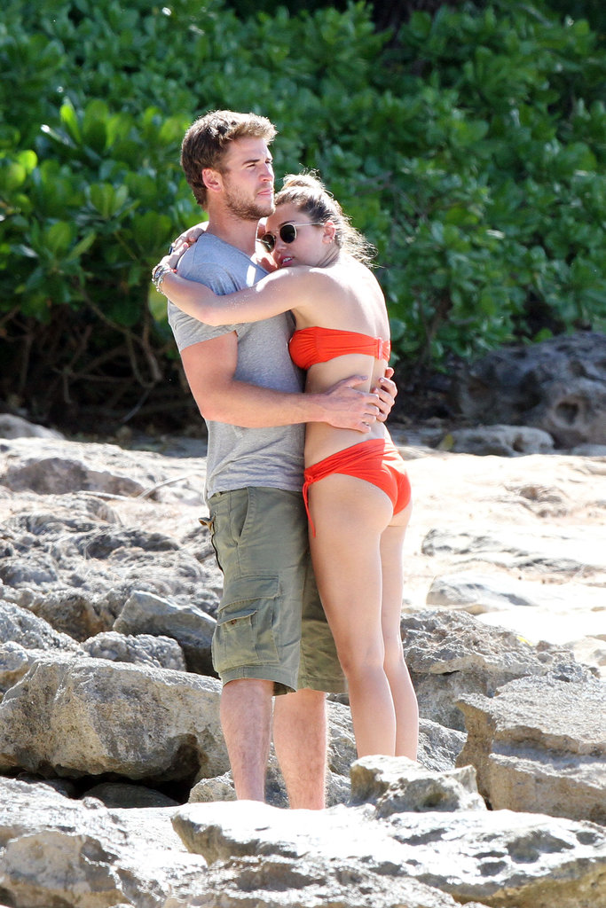 Miley Cyrus and Liam Hemsworth embraced on the beach during a December 2011 Hawaiian vacation.