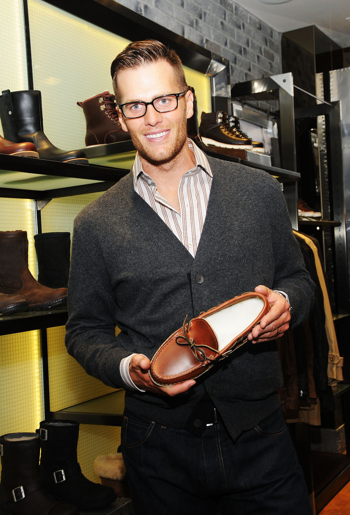 Tom Brady held up an Ugg shoe at the opening of Ugg For Men in NYC.