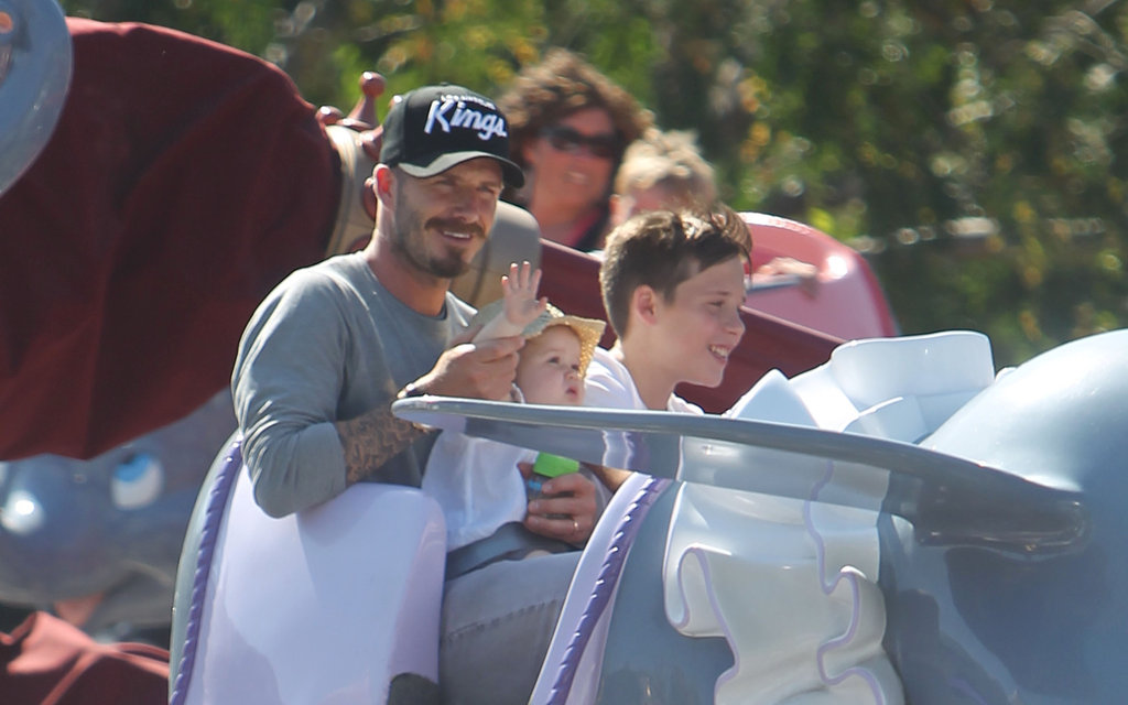 David Beckham waved for Harper Beckham on his lap with Brooklyn Beckham next to them on a ride at Disneyland.
