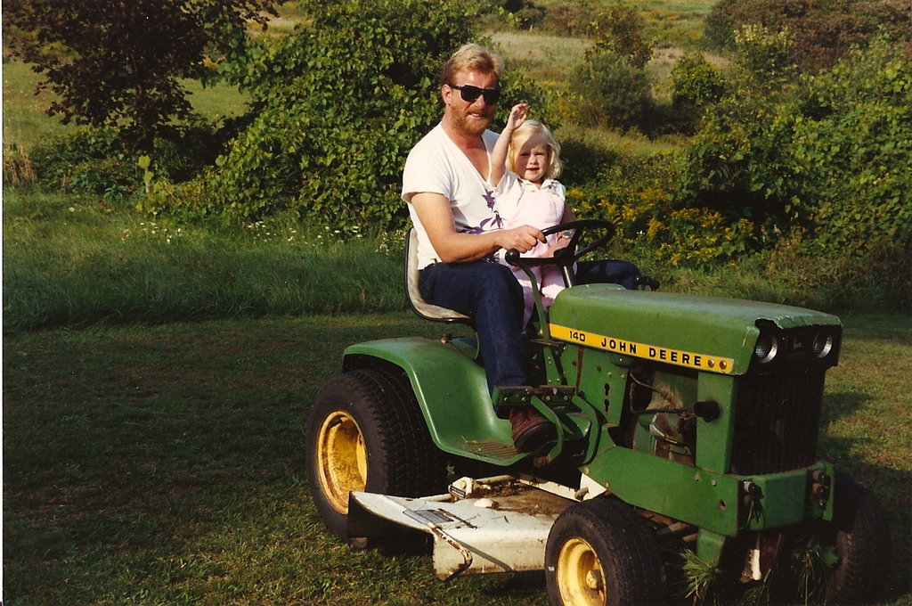 """Here is a photo of my dad and me in the late '80s doing some typical lawn maintenance. You'll notice that he is rocking a printed deep v-neck and some fierce Ray-Ban aviators with his dark-wash jeans, whereas I'm years ahead of my time in pastel denim paired with a simple white tee. We were definitely stylin' in the countryside of Connecticut."" — Grace Hitchcock, assistant community manager"
