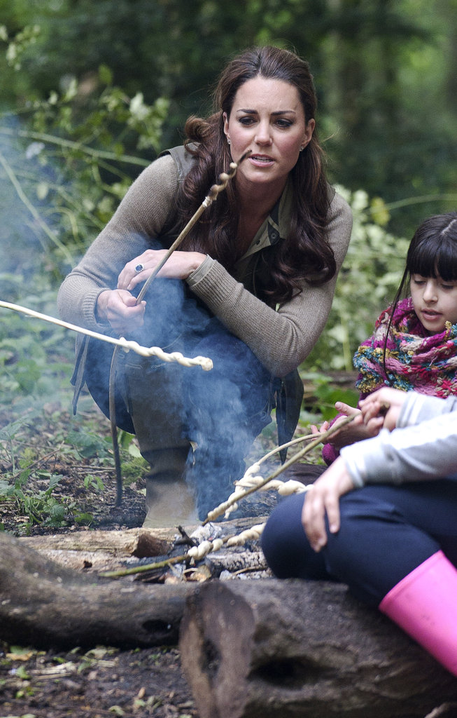 Kate Middleton sat by a fire with children from Expanding Horizons' primary school outdoor camp.