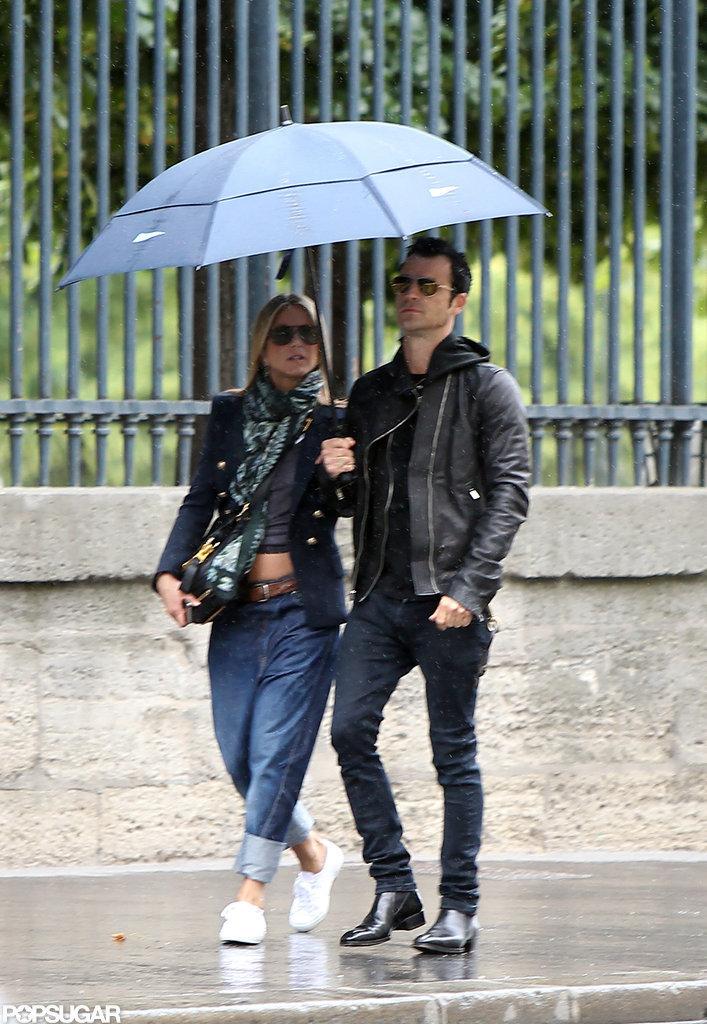 Jennifer Aniston and Justin Theroux braved the Paris rain.