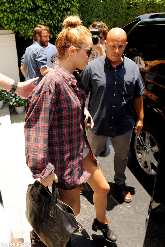 Miley Cyrus checked out of her Miami hotel with friend Cheyne Thomas following behind.