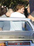 Liam Hemsworth took a seat on a car while hanging out on the set of Empire State.