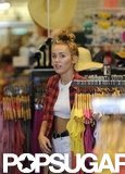 Miley Cyrus wore her hair in a high bun as she shopped with friends in LA.