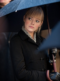 Emma's character, Gwen, wearing a chic houndstooth blouse, black coat, and black leather gloves.  7338130