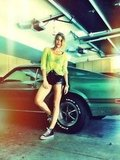 Miley Cyrus posed on a car in short shorts and sneakers. Source: Twitter user MileyCyrus