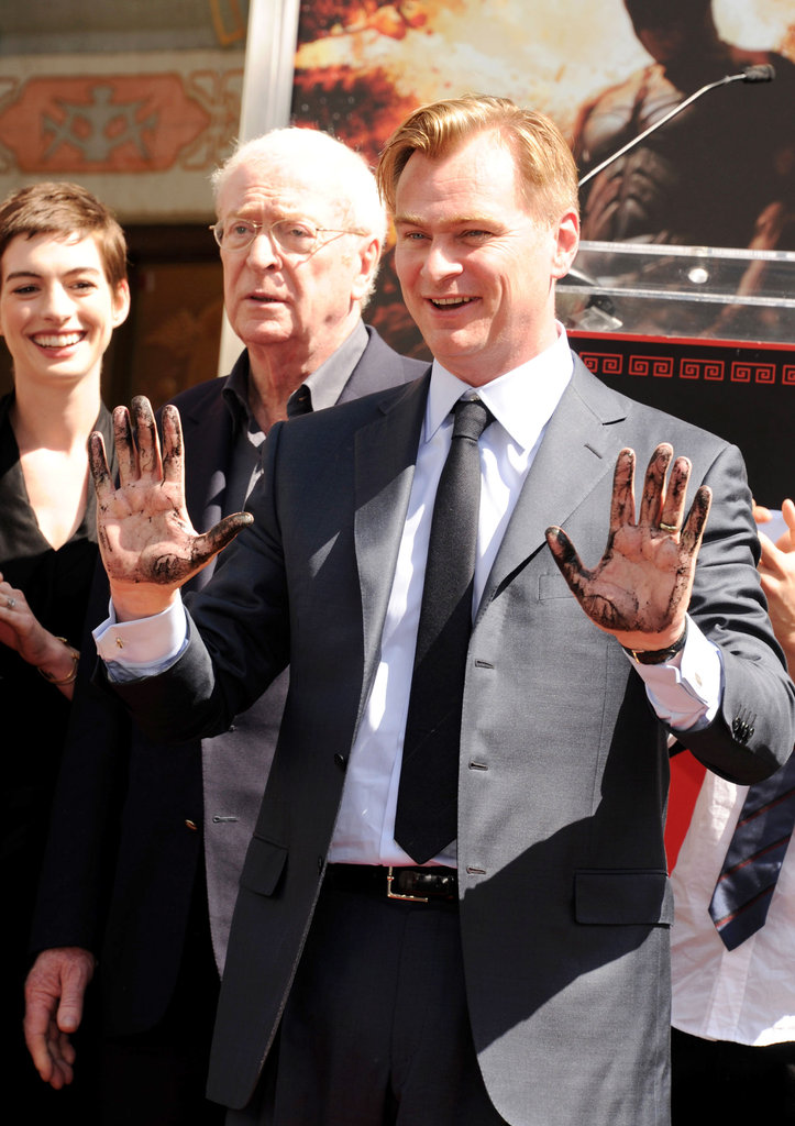 Christopher Nolan was supported by Anne Hathaway and Michael Caine at his hand and footprint ceremony in LA.