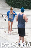 Miley Cyrus adjusted her blue sweatshirt while skateboarding with fiance Liam Hemsworth.